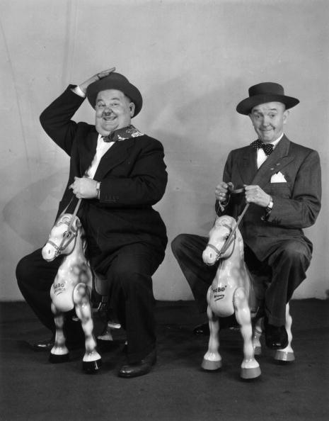 May 1947: Comedian and actor Oliver Hardy (left) and his partner Stan Laurel on a pair of wooden horses. (Photo by Reg Birkett/Keystone Features/Getty Images)